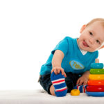 A little boy is playing with toys on the blanket; on the white background